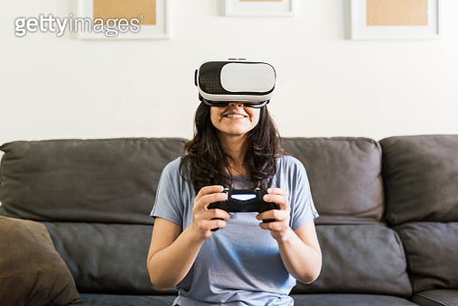 Woman playing a video game with a controller and VR glasses at home - gettyimageskorea