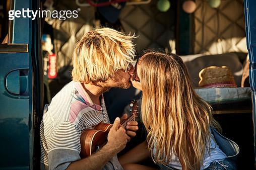 Couple kissing while sitting in doorway of van - gettyimageskorea