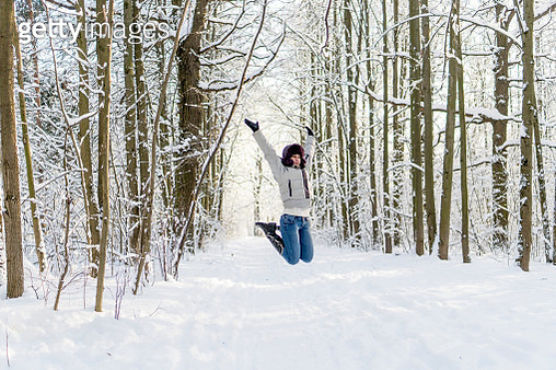 Woman Jumping Over Snowy Field Against Bare Trees In Forest - gettyimageskorea