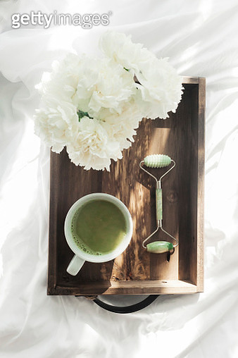 Overhead view of matcha tea with jade roller and flowers in wooden tray on bed - gettyimageskorea