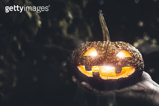 Cropped Hand Of Person Holding Illuminated Jack O Lantern During Halloween - gettyimageskorea