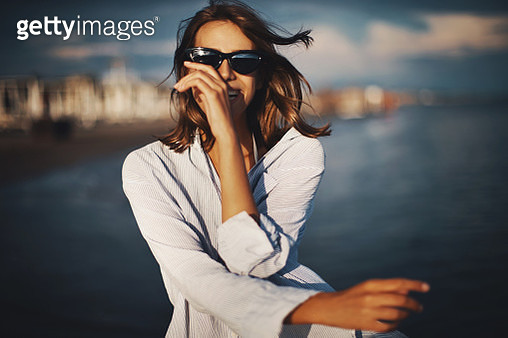 Closeup front view of an attractive mid 20's brunette walking on the beach at sunset and flirting with the camera. She's wearing men's shirt and sunglasses. - gettyimageskorea