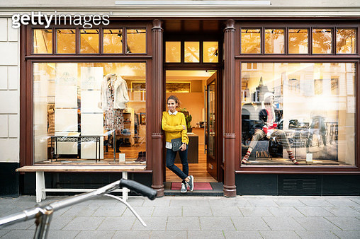 Young woman standing in door of a fashion store, holding laptop - gettyimageskorea