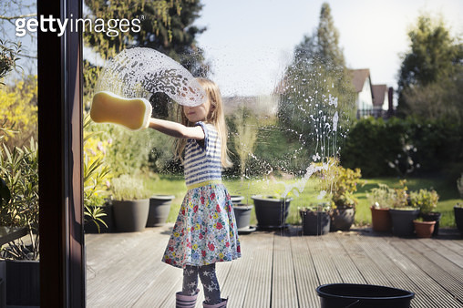 Child (6-7) washing patio window with sponge and soapy water, outside on a sunny day - gettyimageskorea