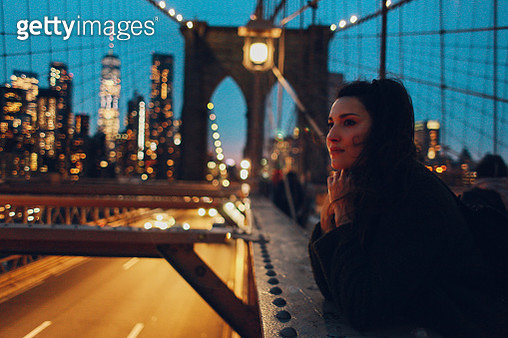 Young woman standing on the Brooklyn bridge, enjoying the amazing view over the NYC skyline at night as the cars bass by beneath. Travel concepts, visiting famous destinations. - gettyimageskorea