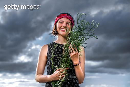 teen girl on sky background with wildflowers - gettyimageskorea