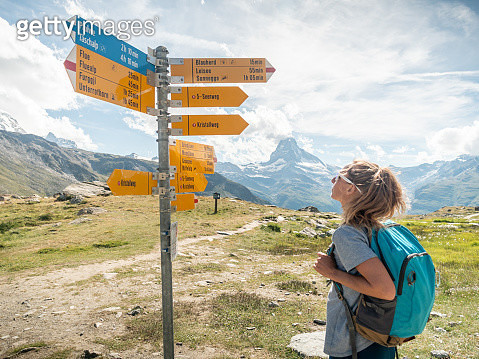 Woman hiker looks at directional signs - gettyimageskorea