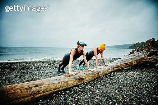 Women doing push ups on log on beach - gettyimageskorea