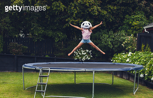 Young girl jumping on trampoline with Panda mask on. - gettyimageskorea