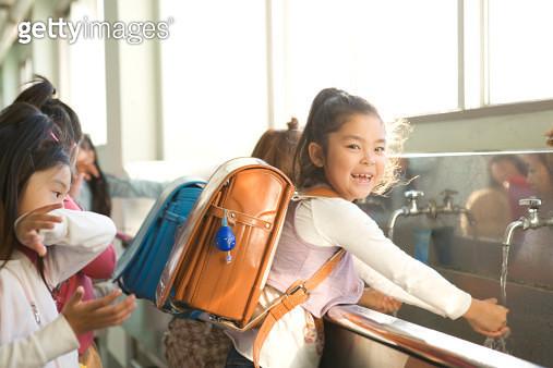 Schoolgirls washing hands, smiling - gettyimageskorea