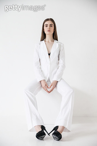 Young woman wearing white suit and shoes sitting on cube with legs apart looking at camera. - gettyimageskorea