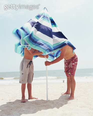 Father and son securing beach umbrella - gettyimageskorea