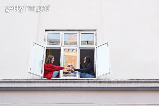 Young female roommates toasting wine glasses outside apartment window - gettyimageskorea