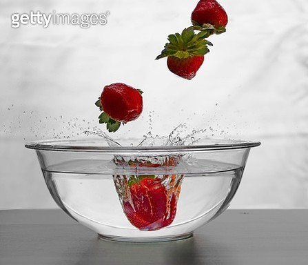 Strawberries Falling In Water Against White Background - gettyimageskorea