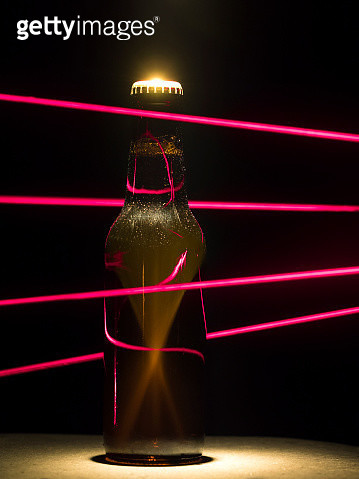 Bottle of beer protected by a trap with beams laser of red color - gettyimageskorea