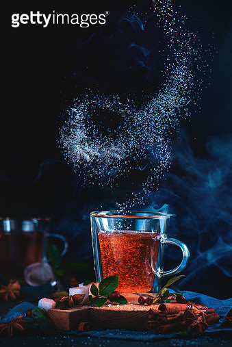 Spiral of sugar above a double wall tea glass. Action food photography. Dynamic teatime on a dark background with copy space. - gettyimageskorea
