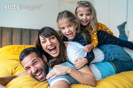 Portrait of family - mother, father and little girls twins smiling and looking at camera - gettyimageskorea