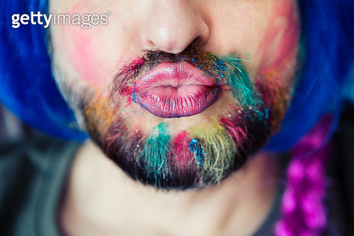 Puckering man wearing multicoloured hair chalk through beard, makeup and wig - gettyimageskorea