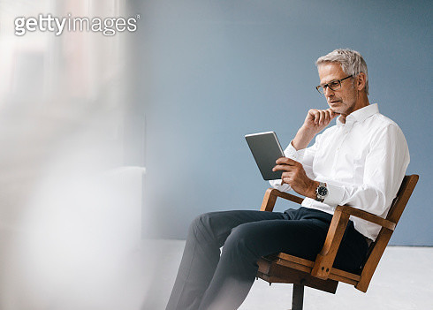 Manager sitting in office, using digital tablet - gettyimageskorea