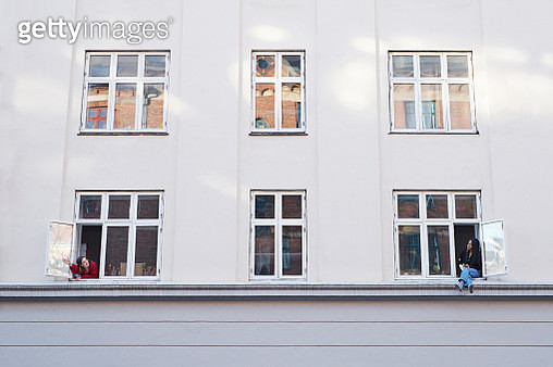 Young female neighbors talking from apartment windows - gettyimageskorea