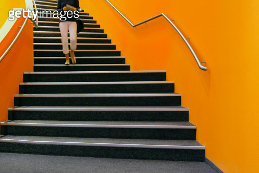 Young person walking down orange stairs - gettyimageskorea