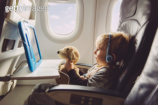 Little boy sitting on an airplane watching something on digital tablet - gettyimageskorea