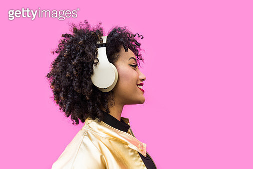 Fashionable Young Woman With Curly Hair Against Pink Background - gettyimageskorea