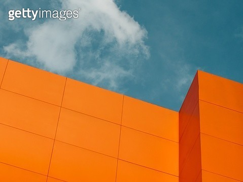 Low Angle View Of Orange Building Against Cloudy Sky - gettyimageskorea