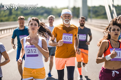 Happy senior man taking a part in marathon race on the road. - gettyimageskorea