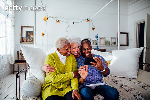 Three mature women sitting on sofa in bedroom, smiling, taking selfie - gettyimageskorea