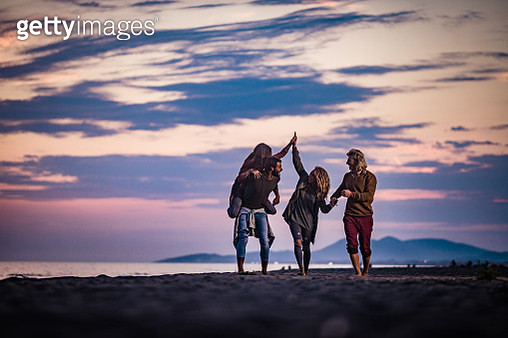 Two playful couples having fun together during autumn vacation on the beach at dusk. Copy space. - gettyimageskorea