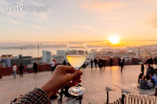 Drinking vinho verde (green wine) with view of Lisbon skyline at Miradouro de Santa Catarina, Portugal - gettyimageskorea