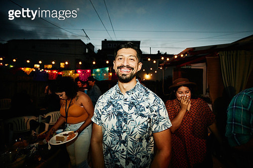 Portrait of smiling man at backyard party with friends on summer evening - gettyimageskorea