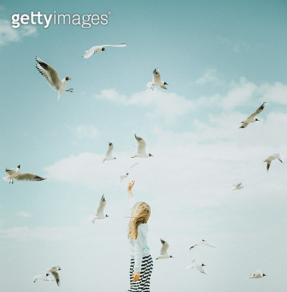 Portrait of a little girl in profile surrounded with seagulls in the sky at the beach. Childhood. Travel with kids. Family vacation. Fineart portrait. - gettyimageskorea