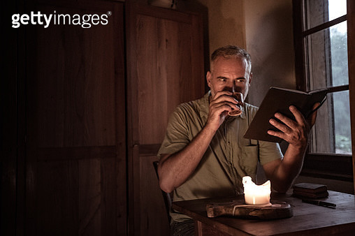 Mature Man Reading a Book Indoors - gettyimageskorea
