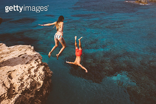 Active couple diving from high cliff into ocean - gettyimageskorea