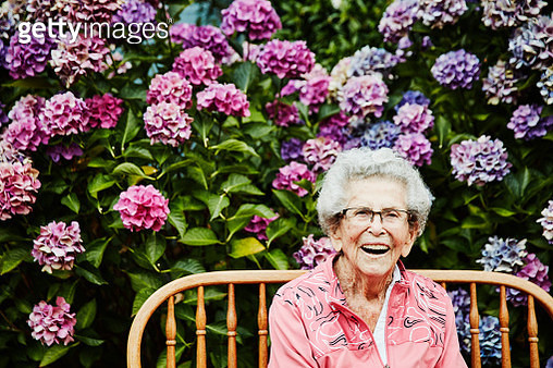 Portrait of laughing senior woman sitting in backyard garden - gettyimageskorea