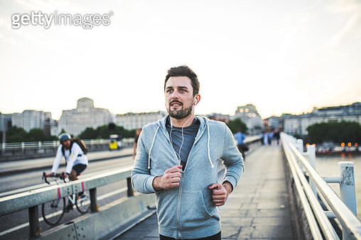 Handsome runner jogging in London, listening to music. - gettyimageskorea