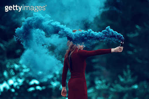 side view of woman in the forest holding flaming torch. - gettyimageskorea