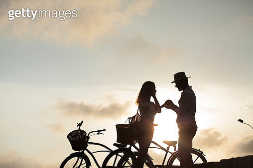 Latin ethnicity couple ages 25-35 are enjoying the sunset on their bicycles in the city of Cartagena - gettyimageskorea