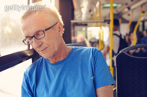 Elderly man napping while traveling in bus. Male passenger is commuting by public transport. - gettyimageskorea