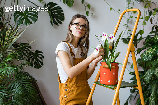 Young Woman Standing By Potted Plant - gettyimageskorea