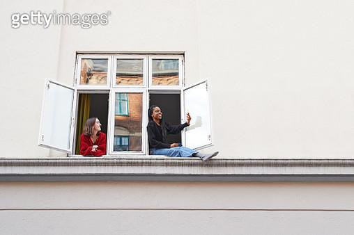 Young women taking selfie in apartment window - gettyimageskorea