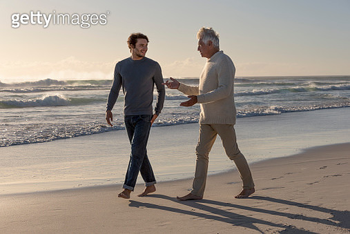 Happy father and son walking on the beach - gettyimageskorea