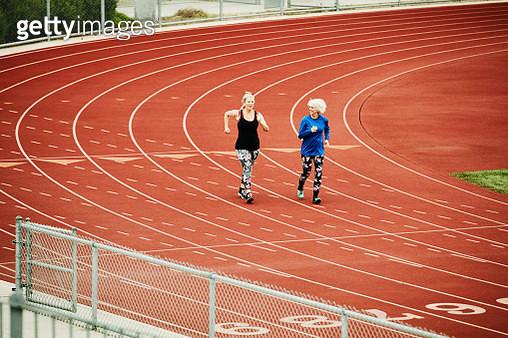 Smiling senior female athletes racewalking on track - gettyimageskorea