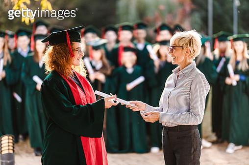 Happy senior professor giving diploma to female student on graduation day. - gettyimageskorea