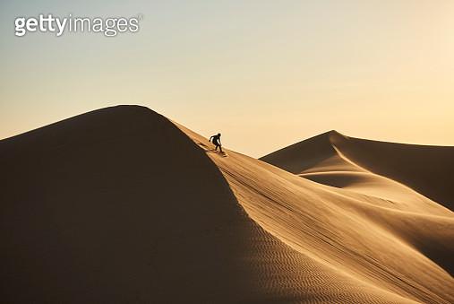 Boy sand surfing in the desert sand dunes - gettyimageskorea