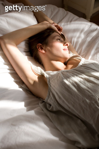 In the morning light a woman in her bed is waking up with a stretch. - gettyimageskorea