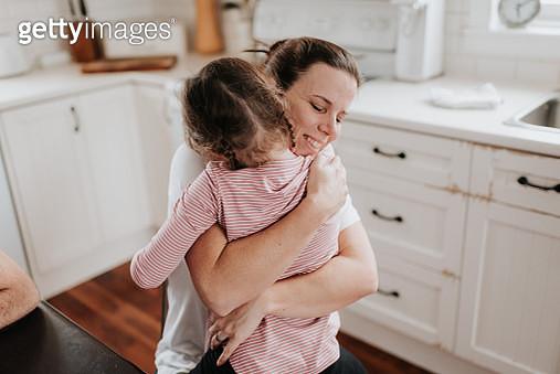Mother hugging daughter in kitchen - gettyimageskorea