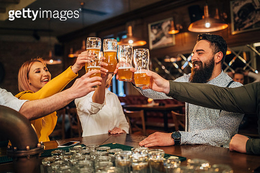 Group of young joyful friends having fun while drinking beer in a pub - gettyimageskorea